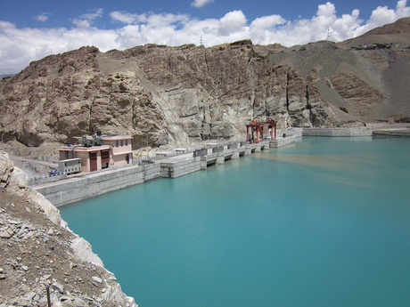 Hydropower plant with mountains in background and water reservoir in foreground